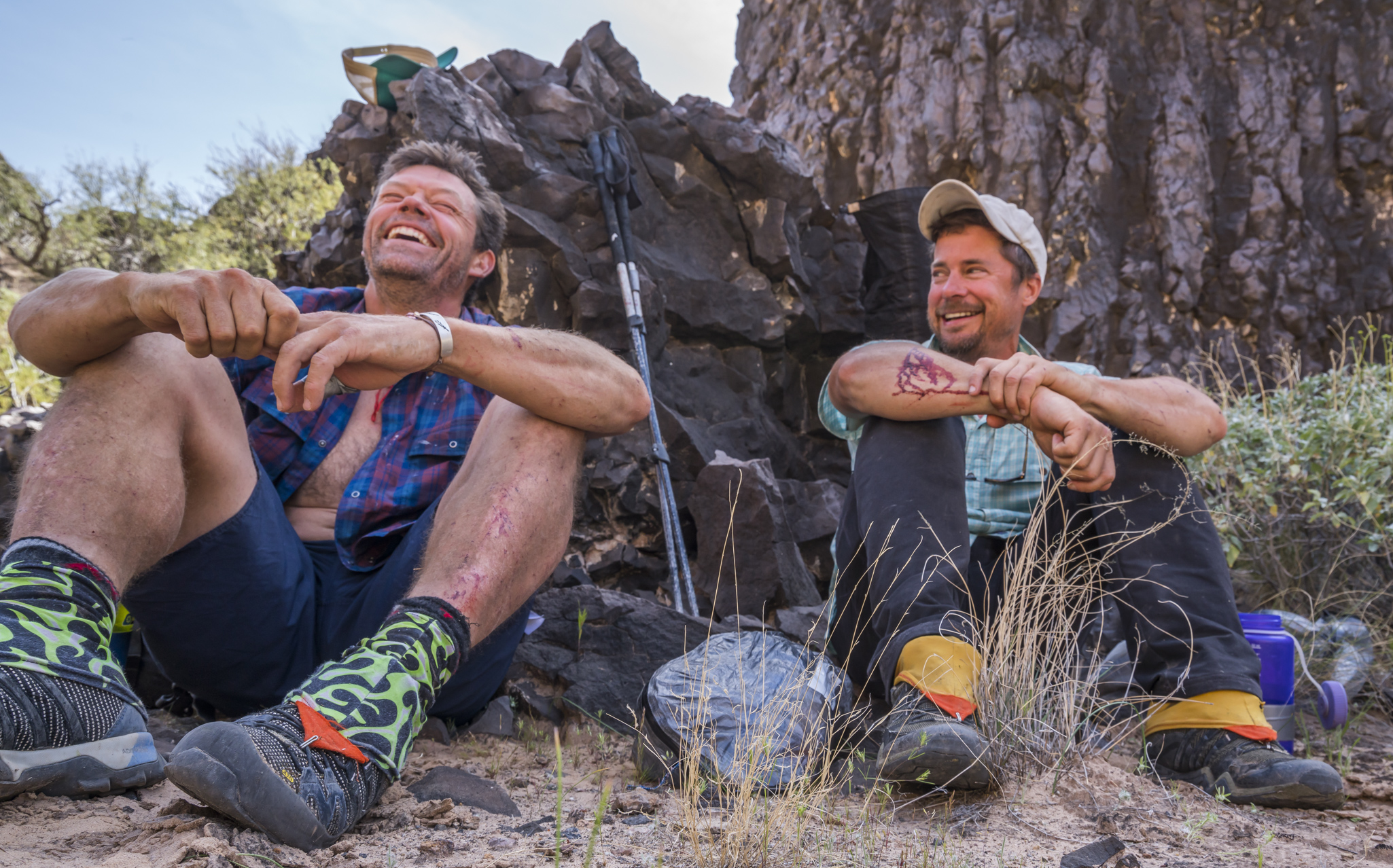 Kevin Fedarko and Pete McBride sit against a rock. They are outfitted in hiking shoes. They laugh.